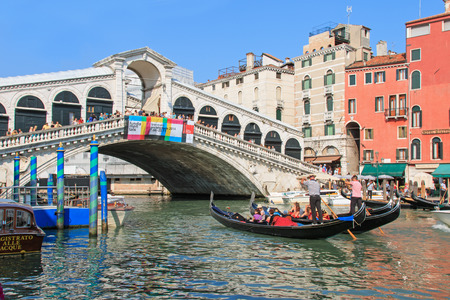 Venice, Italy - June 28, 2014: Gondolas and small boats on the Grand Canal in Venice, Italy, close to Rialto bridge. Some tourists admiring the stunning view.