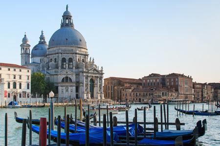 Venice, Italy - June 28, 2014: Traditional Gondolas on Canal Grande with Basilica di Santa Maria della Salute in the background in Venice, Italy