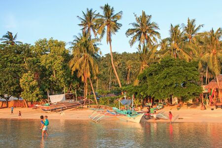 Corong Corong, Philippines - January 12, 2015: Kids playing on the beach at sunset in Corong Corong, Palawan, northern part of the Philippines. photo