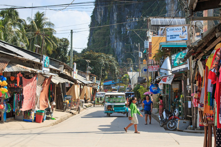 palawan: El Nido, Palawan - January 16, 2015: main street of El Nido in Palawan, one of the main islands in the Philippines. Tricycles and local people on foreground.