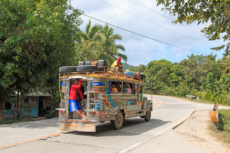 filipino ethnicity: Puerto Princesa, Philippines - January 12, 2015: People in colorful traditional bus jeepney in Palawan, one of the 7107 isalnds of the Philippines. Jeepney are used as a very cheap mean of transportation in the Philippines