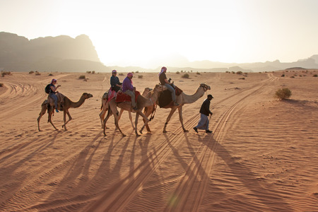 camping tent: Wadi Rum, Jordan - March 24,2015: Tourists riding camels at sunset in the Wadi Rum desert, Jordan