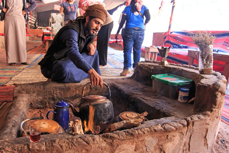Wadi Rum, Jordan - March 24,2015: Bedouin serving tea to the tourists visiting the bedouin camp in the Wadi Rum desert, Jordan
