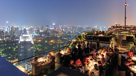 Bangkok, Thailand - April 15,2015: Bangkok by night viewed from a roof top bar with many tourists enjoying the scene Redakční