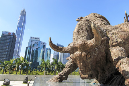Shenzhen, China - August 19,2015: Stock market building in Shenzhen, one of the three stock markets in China, with the copper bull statue on foreground. The others two Stock Markets of China are in Hong Kong and Shanghai. Redakční