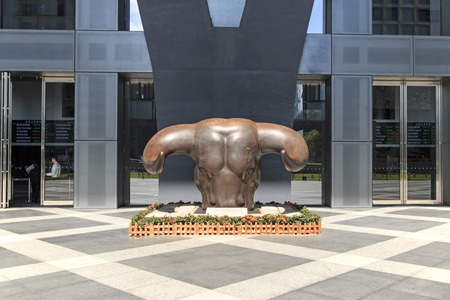 hing: Shenzhen, China - August 19,2015: Stock market building in Shenzhen, one of the three stock markets in China, with the copper bull statue on foreground. The others two Stock Markets of China are in Hong Kong and Shanghai. Editorial