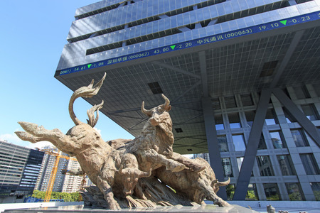 Shenzhen, China - August 19,2015: Stock market building in Shenzhen, one of the three stock markets in China, with the copper bull statue on foreground. The others two Stock Markets of China are in Hong Kong and Shanghai. Stock Photo - 44158566