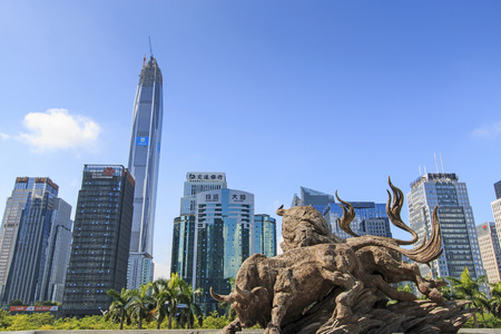 wallstreet: Shenzhen, China - August 19,2015: Stock market building in Shenzhen, one of the three stock markets in China, with the copper bull statue on foreground. On background the tallest building of Shenzhen: the Ping An IFC