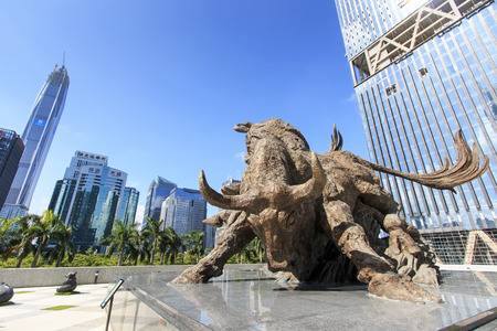 Shenzhen, China - August 19,2015: Stock market building in Shenzhen, one of the three stock markets in China, with the copper bull statue on foreground. The others two Stock Markets of China are in Hong Kong and Shanghai. Publikacyjne