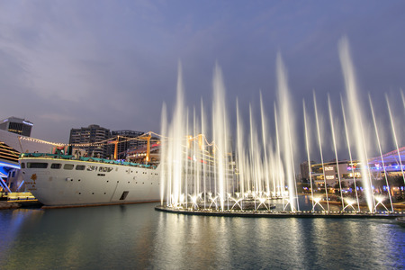 renamed: Shenzhen, China - August 22,2015: Dancing Fountains in New Sea World Plaza, one of the landmark of Shenzhen, at sunset with the Minghua ship on its center. The ship was originally known as Anceevilla and  was later renamed Minghua by the chinese who bough
