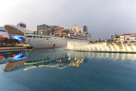 Shenzhen, China - August 22,2015: Dancing Fountains in New Sea World Plaza, one of the landmark of Shenzhen, at sunset with the Minghua ship on its center. The ship was originally known as Anceevilla and  was later renamed Minghua by the chinese who bough