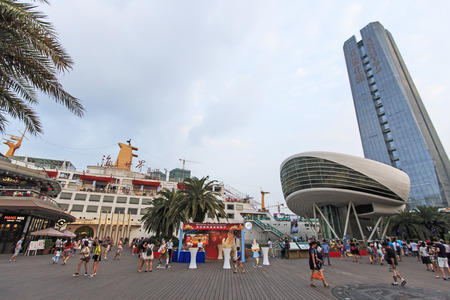 renamed: Shenzhen, China - August 22,2015: Tourists walking in New Sea World Plaza, one of the landmark of Shenzhen, at sunset with the Minghua ship on its center. The ship was originally known as Anceevilla and  was later renamed Minghua by the chinese who bought Editorial