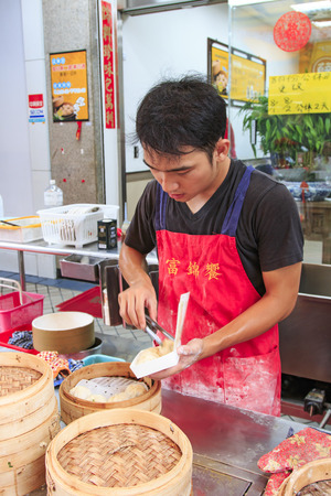 invented: Kaohsiung, Taiwan - August 9,2015: Street food vendor in Kaohsiung, Taiwan, preparing the steamed Xiao Long Bao, a traditional chinese dish invented in Shanghai Editorial