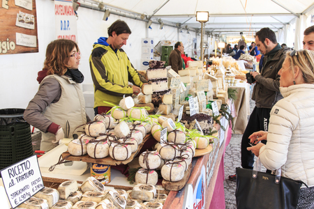 italy: Moncalvo, Italy - October 18,2015: Tourists in front of a cheese vendor at the Truffle fair of Moncalvo, Italy