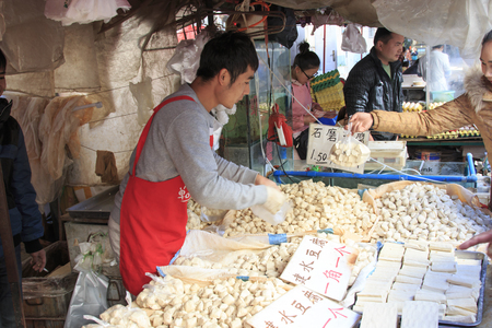 kunming: Kunming, China - January 9, 2016: Man selling different varieties of tofu in a market in Kunming, China Editorial