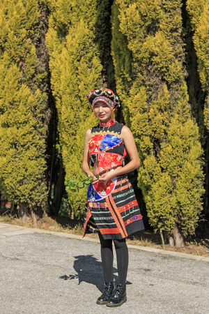 attire: Kunming, China - January 7, 2016: Young girl dressed with the traditional attire of Yunnan, in China
