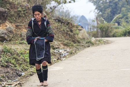 aboriginal woman: Sapa, Vietnam - February 16, 2016: Aboriginal woman of the mountains of Sapa, in north Vietnam, dressed with the traditional attire walking to her village