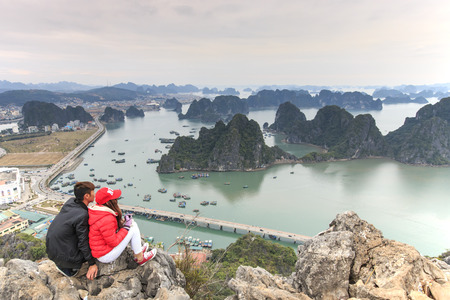Hanoi, Vietnam: February 24, 2016: Young couple enjoying the view of Halong Bay from the top of the mountain