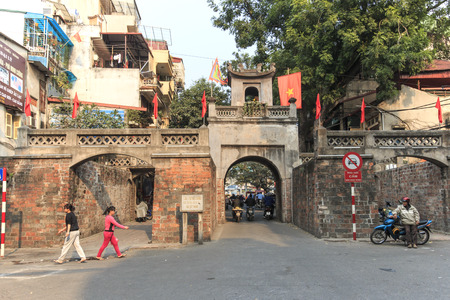 motorcycle officer: Hanoi, Vietnam: February 21, 2016: People walking in front of the Quan Chuong Gate in the Old Quarter of Hanoi