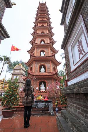 Hanoi, Vietnam - February 23, 2016: Woman praying in fron of the Tran Quoc Pagoda in Hanoi, Vietnam Editorial