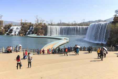 Kunming, China - March 4, 2016: Tourists wisiting the Kunming Waterfall park featuring a 400 meter wide manmade waterfall. Kunming is Yunnans capital Editorial