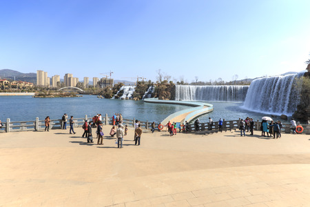 kunming: Kunming, China - March 4, 2016: Tourists wisiting the Kunming Waterfall park featuring a 400 meter wide manmade waterfall. Kunming is Yunnans capital Editorial