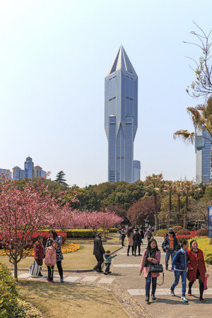 futures: Shanghai, China - March 26, 2016: Tourists walking in Peoples Park one of the busiest in Shanghai. Tomorrow Square skyscraper on background Editorial
