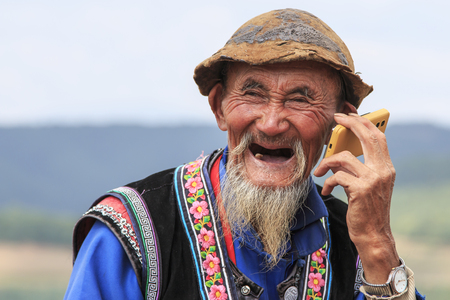 Dongchuan, China - September 27, 2016: An old chinese man dressed with the traditional attire using a telephone while enjoying the panorama of DongChuan in Yunnan Province, China