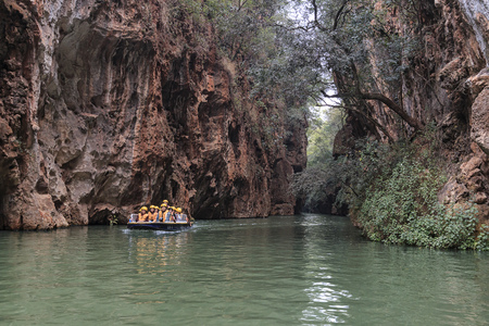 thee: Jiuxiang, China - March 29, 2017: Tourists on a boat in the river in the Jiuxiang scenic area in Yunnan in China. Thee Jiuxiang caves area is near the Stone Forest of Kunming Stock Photo