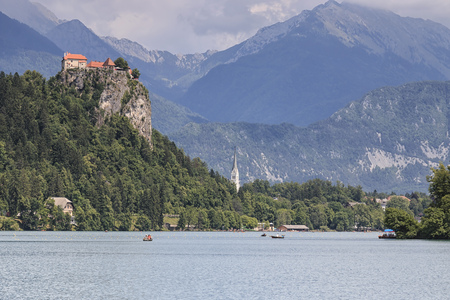 Bled, Slovenia - June 3, 2017: Tourists on small boats in Lake Bled with Bled Castle on background. Editorial