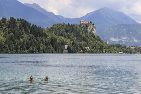 Bled, Slovenia - June 3, 2017: People swimming in Lake Bled with Bled Castle on background.