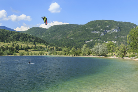 Bohinj, Slovenia - June 4, 2017: Tourist paragliding on lake Bohinj a famous destination not far from lake Bled, in Slovenia. Editorial