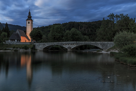 Bohinj, Slovenia - June 5, 2017: Church of St John the Baptist in Lake Bohinj, a famous destination not far from lake Bled in Slovenia, at sunset.