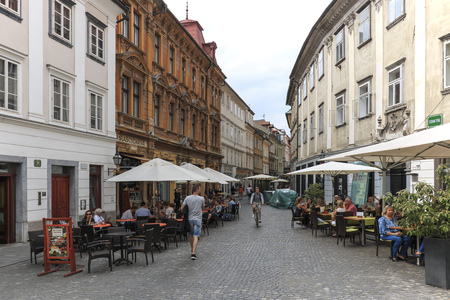 Ljubljana, Slovenia - June 6, 2017: Street in the center of Ljubljana and several tourists passing by Editorial