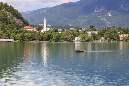 Bled, Slovenia - June 3, 2017: Close up of the church in the center of Bled Lake with a small boat on foreground