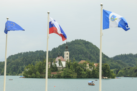 Bled, Slovenia - June 3, 2017: Close up of the church in the center of Bled Lake with several tourists on a boat