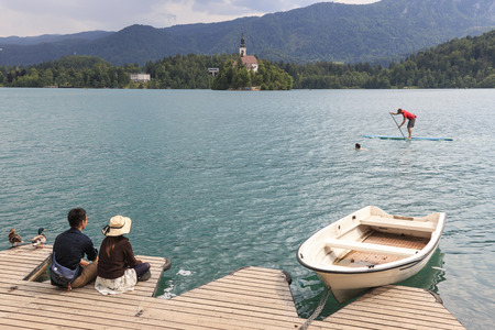 Bled, Slovenia - June 3, 2017: Tourists sitting on the bank of lake Bled.