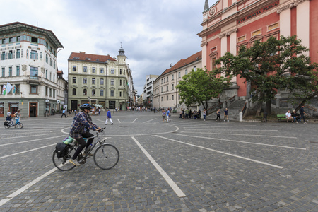 Ljubljana, Slovenia - June 6, 2017: View of the main square of Ljubljana and Ljubljana Cathedral and several tourists passing by