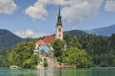 Bled, Slovenia - June 3, 2017: Close up of the church in the center of Bled Lake with several tourists walking by