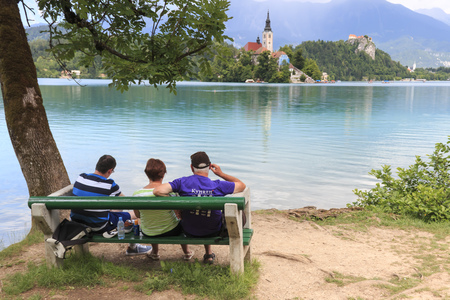 john the baptist: Bled, Slovenia - June 3, 2017: Tourists sitting on a bench on the bank of lake Bled. Church of background Editorial