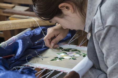 Dali, China - March 23, 2018: Chinese woman from the Bai minority weaving silk