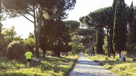 Man running over the ruins of the ancient Via Appia (Appian Way) in Rome