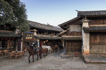 Shaxi, China - February 21, 2019: Horses riding in the center of Shaxi old town at dusk
