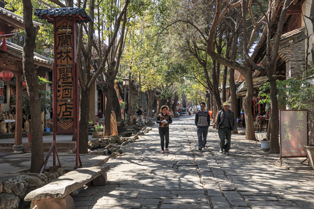 Shaxi, China - February 21, 2019: Chinese tourists walking in one of the streets of Shaxi old Town along the ancient Tea Horse Road (South Silk Road)