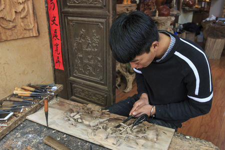 Shaxi, China - February 21, 2019: Chinese artist carving a wood plate in Shaxi old town Reklamní fotografie