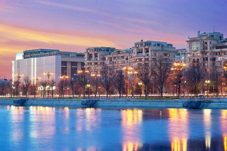 bucuresti: Bucharest Unirii Boulevard. Sunset Sky and Night Lights Reflection Dambovita River. Stock Photo