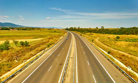 highroad: Highway landscape with field, forest and mountains in Romania.