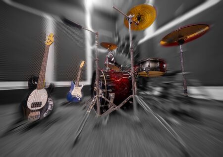 Drums and guitars in music rehearsal room.