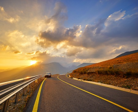 highroad: Sunset on Transalpina Highway in Romanian Mountains. Stock Photo
