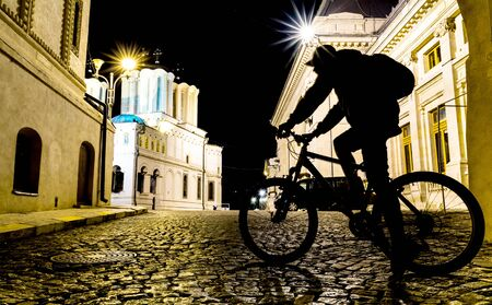 packer: Night scene with shadow of a back packer cyclist on old street in Bucharest. Stock Photo